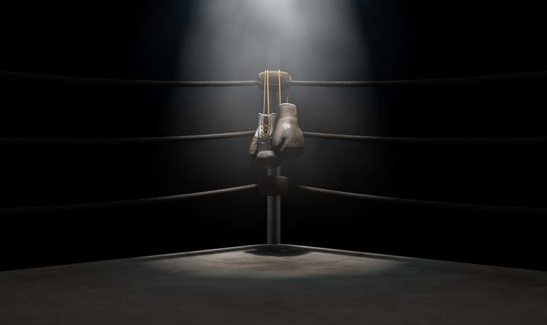 A closeup of the corner of an old vintage boxing ring surrounded by ropes spotlit by a spotlight on an isolated dark background.