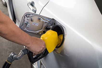 Adult white male filling his car with gas from a yellow colored nozzle.