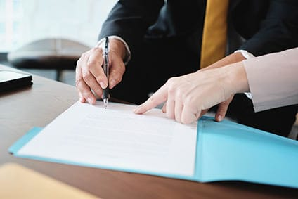 Close up of two sets of adult hands reviewing insurance papers and pointing to a signature.